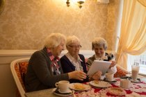 Старшие друзья используют цифровой планшет во время завтрака дома — стоковое фото