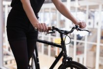 Mid section of female executive walking with cycle in office — Stock Photo