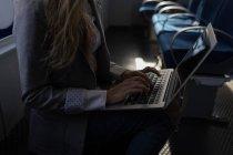 Seção intermediária da mulher usando o laptop em navio de cruzeiro — Fotografia de Stock