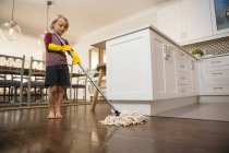 Boy washing the floor with mop at home — Stock Photo