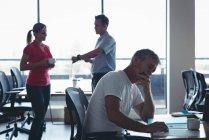 Бизнесмен, работы во время коллег, взаимодействующих друг с другом в офисе — стоковое фото