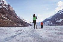 Donna che cattura foto con il telefono cellulare su un paesaggio innevato — Foto stock