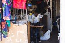 Кравець пошиттям одягу швейні машини магазині — стокове фото