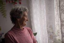 Femme âgée réfléchie souriant à la maison — Photo de stock