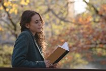 Young woman holding a book in the park — Stock Photo