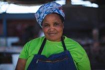Усміхнене жіночий м'ясника, стоячи на магазин м'яса — стокове фото