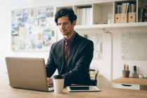 Male executive working on laptop in office — Stock Photo