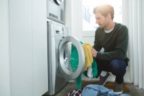 Homme mettre des vêtements dans la machine à laver à la maison — Photo de stock