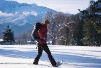 Femme qui marche sur le paysage enneigé, par une journée ensoleillée — Photo de stock
