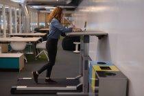 Esecutivo femminile che utilizza laptop sul tapis roulant in ufficio — Foto stock