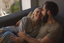 Pareja abrazándose en la sala de estar en casa - foto de stock