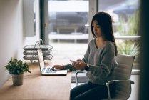 Femme exécutive utilisant un téléphone portable tout en travaillant sur un ordinateur portable au bureau — Photo de stock