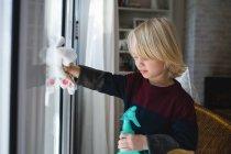 Garçon nettoyage fenêtre avec chiffon à la maison — Photo de stock