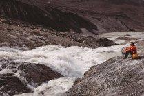 Escursionista maschio con zaino relax vicino al fiume — Foto stock