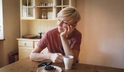 Femme réfléchie prenant le petit déjeuner à la maison — Photo de stock
