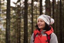 Donna felice in piedi con lo zaino durante l'inverno — Foto stock