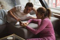 Couple utilisant un téléphone portable dans le salon à la maison — Photo de stock