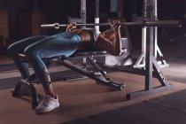 Fitte Frau beim Hantelheben in der Turnhalle — Stockfoto