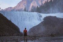 Rear view of man looking at waterfall — Stock Photo