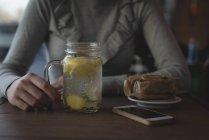 Розділ середині одна жінка, лимонний чай в кафе — стокове фото