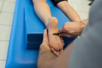 Physiotherapist giving leg massage to woman in clinic — Stock Photo