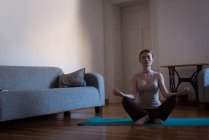 Young woman meditating in yoga posture at home — Stock Photo
