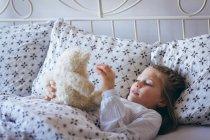 Fille jouer avec ours en peluche sur le lit dans la chambre — Photo de stock