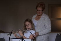 Girl playing flute with her grandmother in living room at home — Stock Photo