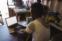 Rückansicht Schneider mit Laptop im Geschäft — Stockfoto