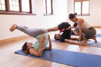 Female trainer assisting woman in yoga exercise at fitness club — Stock Photo