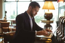 Hombre de negocios usando la laptop cerca de contador en el hotel - foto de stock