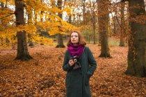 Женщина, держащая старинные камеры в парке в течение осени — стоковое фото