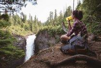 Femme assise près d'une cascade et buvant de l'eau par une journée ensoleillée — Photo de stock
