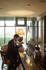 Homme d'affaires à l'aide de portable près de compteur dans l'hôtel — Photo de stock