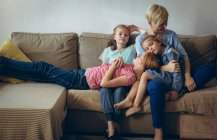 Mother and kids relaxing on sofa in living room — Stock Photo