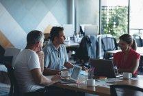 Pessoas de negócios interagindo uns com os outros em reunião no gabinete — Fotografia de Stock