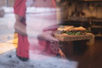 Mittleren Bereich der männlichen Kellner Holding Sandwich im café — Stockfoto
