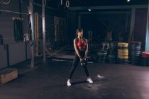 Fit woman exercising with quettlebell in the gym — стоковое фото
