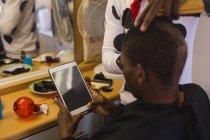 Kunden, die mit digitalen Tablet beim Barbier Trimmen seine Haare im Friseursalon — Stockfoto