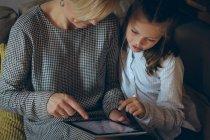 Mère et fille utilisant une tablette numérique à la maison — Photo de stock