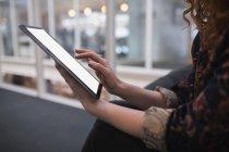 Sección media del ejecutivo femenino usando tableta digital en la oficina - foto de stock