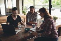 Collègues de travail travaillant sur ordinateur portable dans la cafétéria du Bureau — Photo de stock