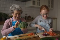 Grandmother and granddaughter cutting vegetables in kitchen at home — Stock Photo