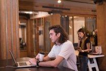 Joven ejecutivo masculino usando laptop en la oficina - foto de stock