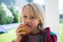 Garçon manger des pommes dans le porche à la maison — Photo de stock