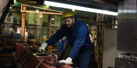 Technician in protective work wear cutting metal in industry — Stock Photo