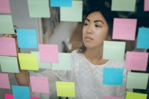 Female executive sticking adhesive notes on glass wall in office — Stock Photo