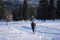 Спортивний жінка, біг на сніжний пейзаж у сонячний день — стокове фото