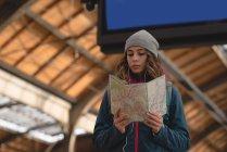 Молодая женщина, глядя на карту на железнодорожном вокзале — стоковое фото