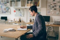 Executive writing note on diary in office — Stock Photo